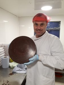 Neil holding huge disc of protein chocolate